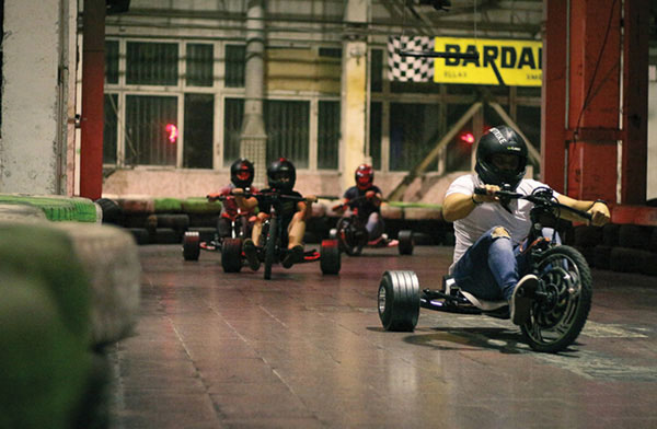People having fun while doing activities at WOLFTRIKE Drift Hall indoor racing track in Riga, Latvia