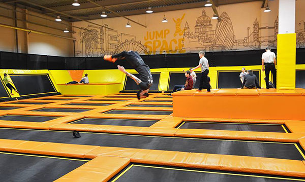 Man exercising on a trampoline in an indoor trampoline park in Riga, Latvia