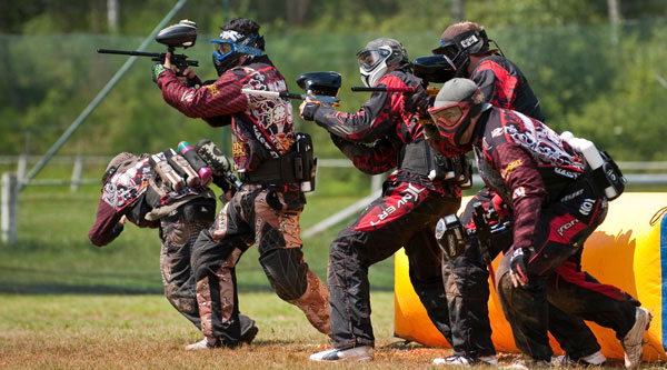 Men paying paintball on an outdoor field in Riga, Latvia